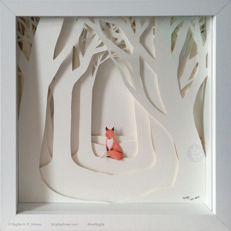 A fox in surrounded by white trees.