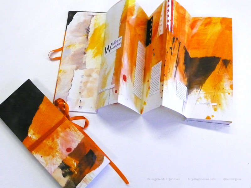 Two concertina books on a table; one closed with a ribbon another open and showing a few of the pages.
