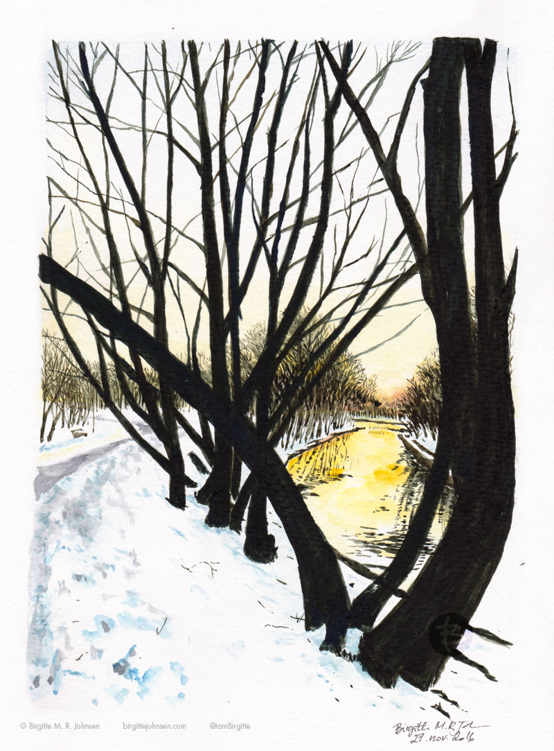 Dark and naked trees stand as a stark contrast to the snow at their base, all reflecting in the river as the sun hangs low in the sky.